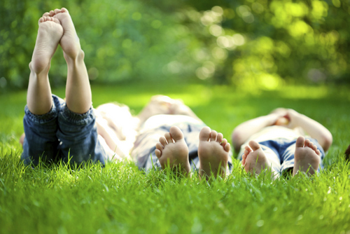 Kids laying in the grass during summer vacation