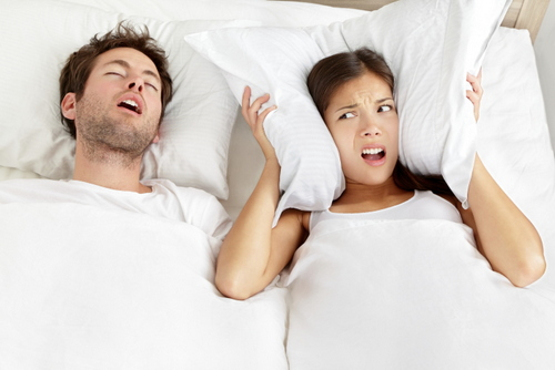 Woman covering ears while man snores in bed